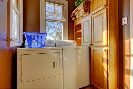 laundry room: Small laundry room with wooden cabinet, white laundry appliances