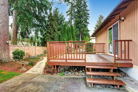 fenced: House with walkout deck. Fenced  backyad with lawn and walkway