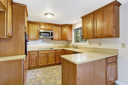 Bright kitchen interior in empty house with linoleum and ivory counter tops photo