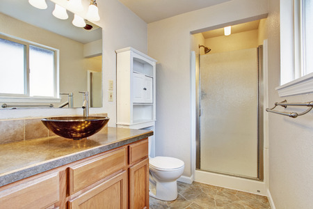 vessel sink: Bathroom interior with glass door shower, wooden vanity with vessel sink and white storage cabinet Stock Photo