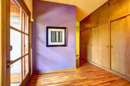 Empty hallway with bright purple wall and glass exit door photo