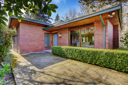 trimmed: Brick house entrance porch with walkway and trimmed hedges alongside Stock Photo