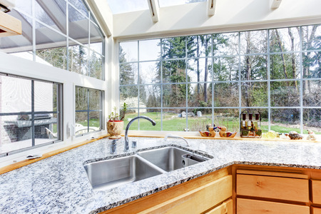 granite kitchen: Bright kitchen corner with glass wall and ceiling. View of steel sink and granite top