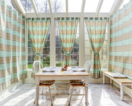 Bright sun room with bench and dining table set