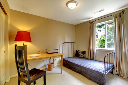furnished apartments: Beige bedroom interior with antique iron frame bed and desk