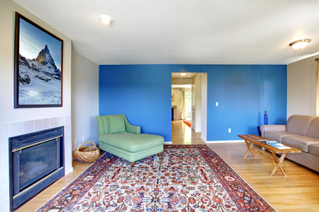 rug: Living room with bright blue  and fireplace. Furnished with green chair, beige sofa and rustic coffee table