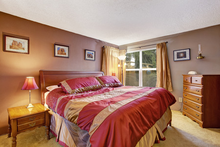 Bedroom interior with beautiful bed in red and mocha, dresser and nightstand photo