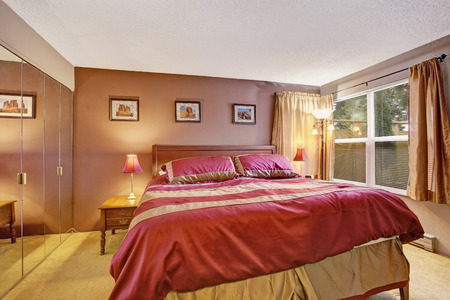 Bedroom interior with beautiful bed in red and mocha and mirror door closet photo