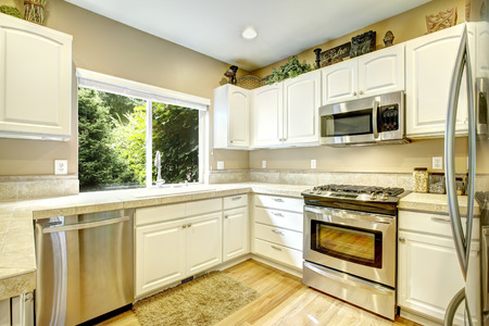 White kitchen cabinets with steel appliances and light tone hardwood floor
