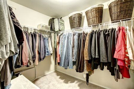 Walk-in closet with clothes on hangers and wicker baskets
