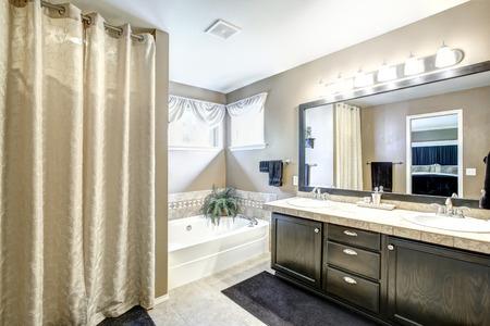 bathroom mirror: Bathroom interior in light grey tones with black vanity cabinet with large mirror. Stock Photo