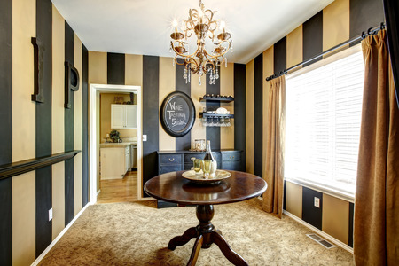 remodeled: Striped wine tasting room with round table and black cabinet