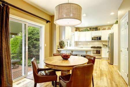 round chairs: White kitchen room with round wood dining table, brown leather chairs. Stock Photo