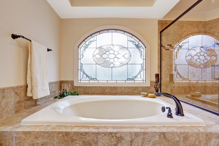 Beautiful bath tub with tile trim in soft ivory and light brown colors.