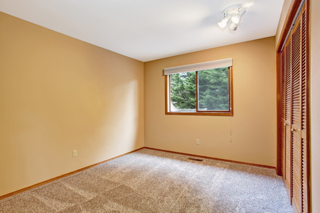 Empty Bedroom Interior In Soft Peach Color With Light Brown Carpet Floor  And Closet Stock Photo