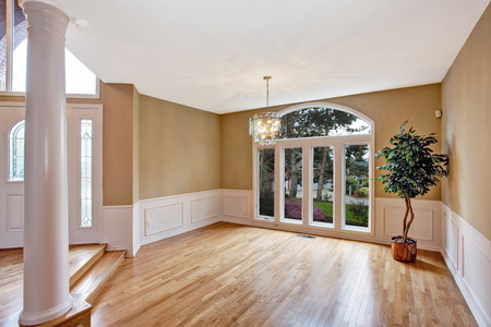 Luxury house interior. Bright  empty hallway with large window and column. Decorated with fake tree in corner