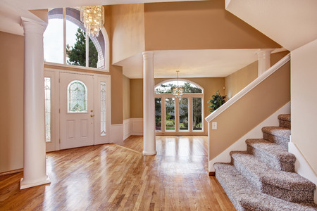 Beautiful entrance hall with high ceiling, columns and arch window in luxury house. photo