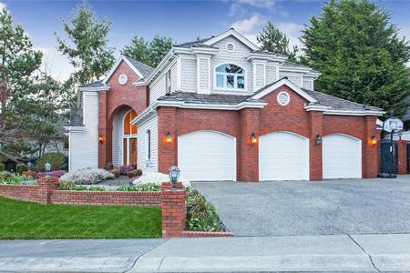Luxe huis buitenkant met rode bakstenen muur bekleding, met drie auto garage en oprit Stockfoto