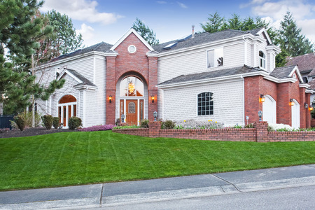 luxury house exterior: Luxury house exterior with red brick wall trim,  with three car garage and driveway