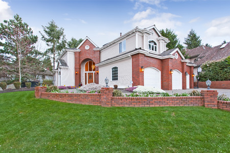 Luxury house exterior with red brick wall trim,  with three car garage and driveway. View of front yard landscape