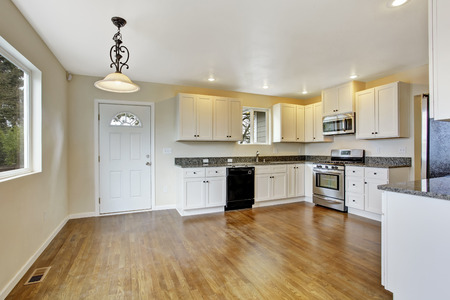 granite kitchen: Interior in empty house. Spacious kitchen room with white cabinets and granite tops Stock Photo