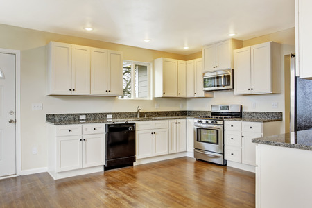 Interior in empty house. Spacious kitchen room with white cabinets, granite tops and steel appliances Stock Photo