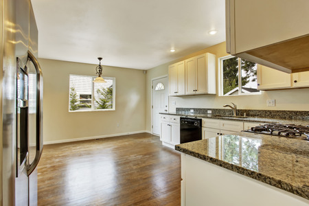 granite kitchen: Interior in empty house . Spacious kitchen room with white cabinets and granite tops