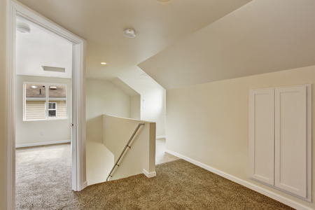 vaulted ceiling: Bright empty hallway with soft brown carpet floor, vaulted ceiling. View of staircase and emtpy room