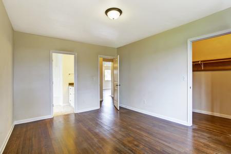 Empty master bedroom interior with hardwood floor. View of bathroom and walk-in closet