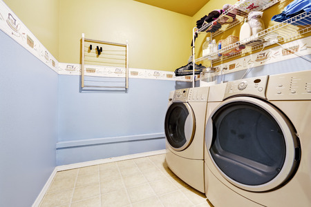 Laudry room interior in light blue and yellow colors. View of washer and dryer