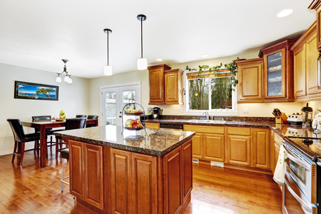 Bright kitchen room interior with island and dining table set