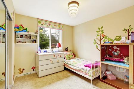 Kinderkamer interieur in zachte ivoor met vloerbedekking. Ingericht met een eenpersoonsbed, dressoir en kast Stockfoto