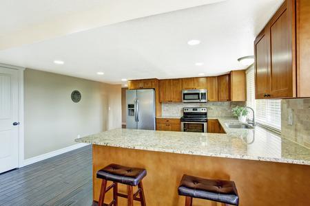 brown granite: Kitchen room with hardwood floor, brown cabinets with granite tops and tile back splash trim