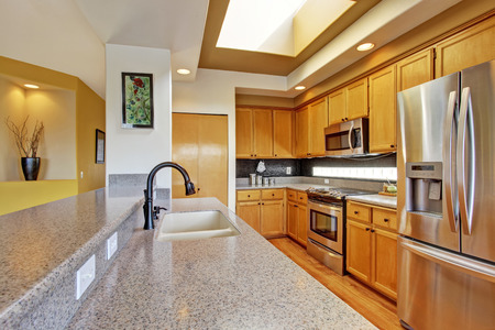 Bright kitchen room with skylight, steel appliances and granite tops