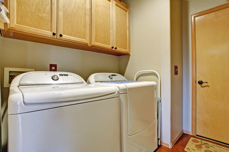 dryer  estate: Simple bathroom interior with white appliances and wooden cabinets Stock Photo
