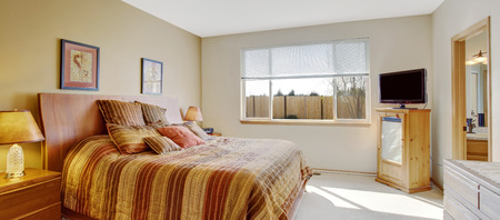 Bright bedroom with cheerful orange striped bed and tv photo