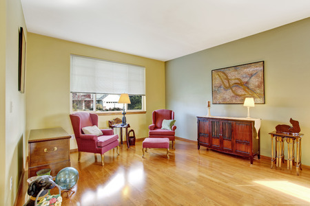 Bright living room with shiny hardwood floor  Furnished with antique  burgundy chairs and cabinet photo