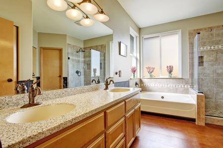 brown granite: Bathroom interior with granite top cabinet, white bath tub and glass door shower