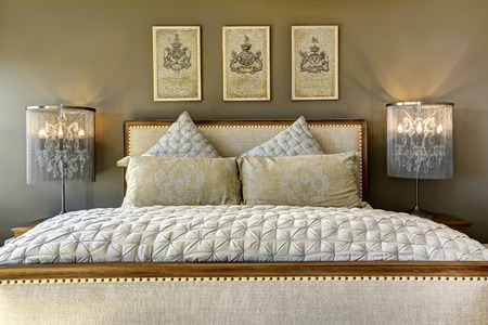 furniture: Luxury bedroom furniture. Carved wood bed with pillows and lamps on nightstands