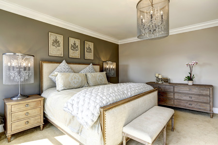 Luxury bedroom interior with carved wood bed, dresser and nightstands