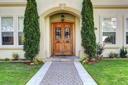 Luxury house entrance porch with wooden door and wrought iron details on it Banque d'images