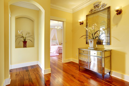 niche: Bright hallway with shiny cabinet, arch niche in wall with decorative flowers Stock Photo