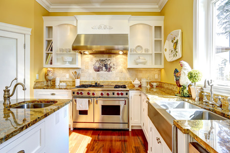 luxury apartment: Bright yellow kitchen interior in luxury house with granite tops and kitchen island. Stock Photo