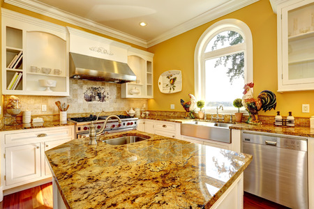 large: Bright yellow kitchen interior in luxury house with granite tops and kitchen island. Stock Photo