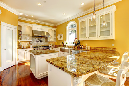 kitchen cabinets: Bright yellow kitchen interior in luxury house with granite tops and kitchen island. Stock Photo