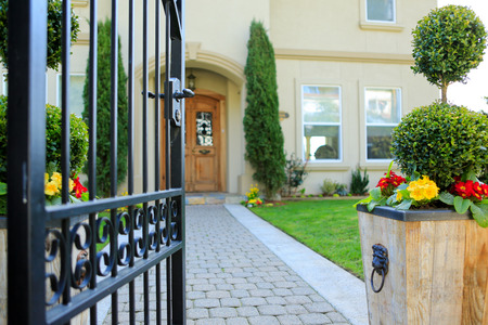 Open entrance iron gate with wooden flower pot with yellow and red flowers Standard-Bild
