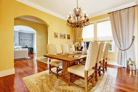 dining table and chairs: Bright luxury dining room with rich carved wood table