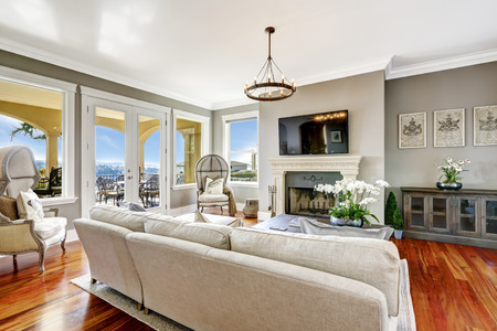Bright luxury living room with fireplace and tv. Corner decorated with antique hood chairs
