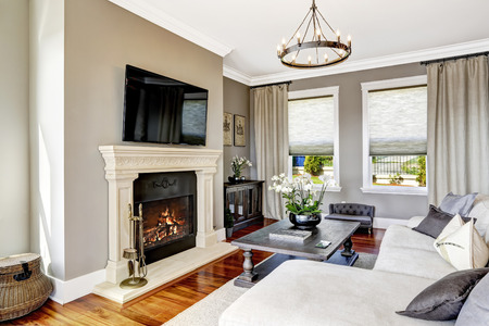 luxury living room: Bright luxury living room with fireplace and tv, white cozy couch and carved wood table with flowers
