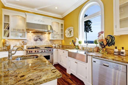 Kitchen cabinets with steel appliances and granite tops. Luxury house interior photo